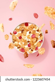 Flying fruits and corn flakes with fresh plum, banana and fig cereal in a bowl full of yogurt.