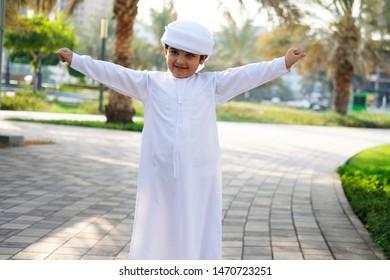Flying gesture by Arab Middle East Muslim boy wearing cultural Kandura kids wear