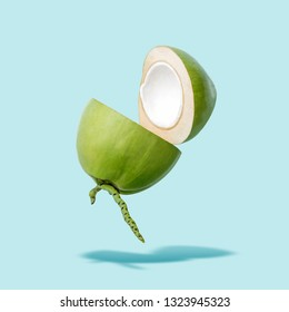 Flying green coconut on a blue background, creative summer food concept, floating young coconut in the air with clipping path