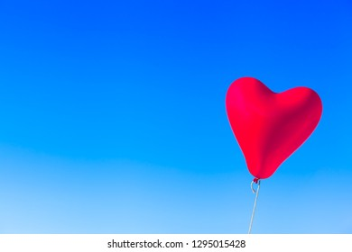 Flying heart shaped red balloon tied by rope at blue sky background (copy space)