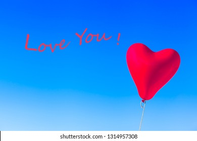 Flying heart shaped red helium balloon tied by rope at blue sky background and wavy textual message - LOVE YOU!