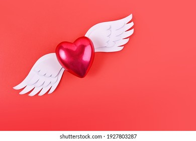 flying heart with wings on a red background