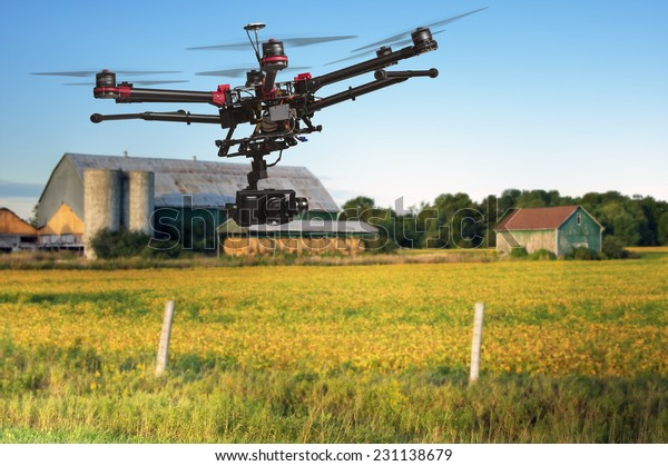 A flying helicopter with raised landing gears and a camera with blurred crop field and farm structures on a background highlighted by a sunset