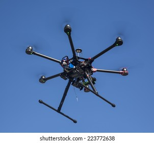 A flying hexacopter without a camera shot from below with the blue sky on the background