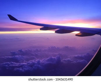 Flying high on the fantastic plane above the white snowy natural clouds, look out from the airplane window. The scenery of the blue horizontal line with landscape view. Travel & Freedom Journey time.
