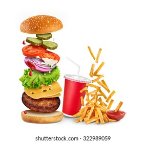 Flying ingredients of hamburger, fried potatoes, ketchup and paper cup isolated on white background.