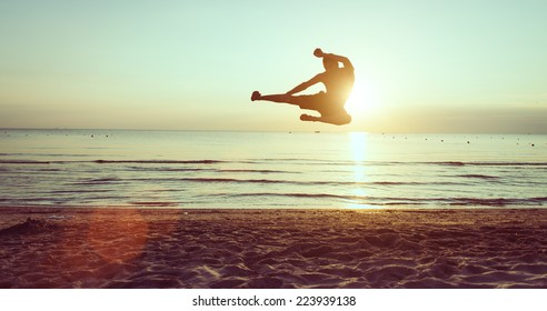 flying kick on the beach at dawn. martial arts and fitness
