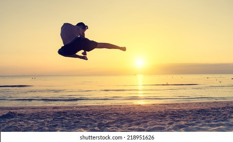 flying kick on the beach at sunrise