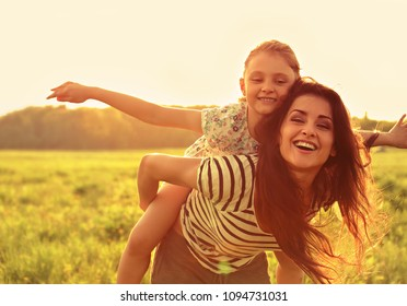 Flying kid girl laughing on the happy enjoying mother back on sunset bright summer background. Closeup portrait.