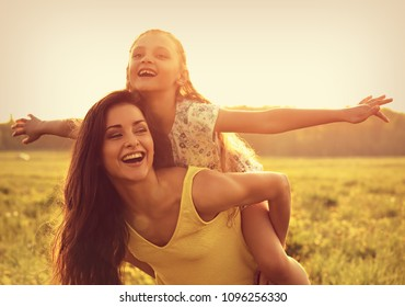 Flying kid girl laughing on the happy enjoying mother back on sunset bright summer background. Closeup toned vintage portrait.