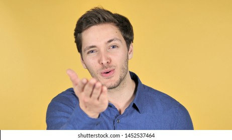 Flying Kiss by Young Man Isolated on Yellow Background