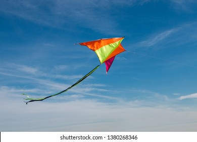 Flying a kite. Bright kite against the blue sky. Sunny day. Sky clouds.