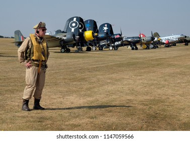 Flying Legends air show, Imperial War Museum, Duxford, Cambridgeshire. UK.14-15 July 2018. Re-enactors in world war two clothing with fighters in the background.