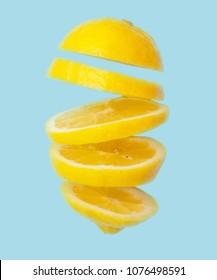 Flying lemon. Sliced lemon isolated on blue background. Levity fruit