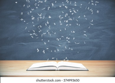 Flying letters from the opened book on wooden table at blackboard background