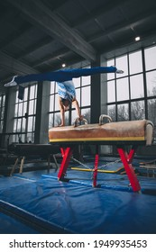 Flying. Little male gymnast training in gym, composed and active. Caucasian fit little boy, athlete in sportswear practicing in exercises for strength, balance. Movement, action, motion, dynamic