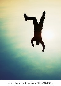 Flying man. Young man falling down on colorful sky background.