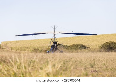 Flying Microlight Landing Airstrip Flying microlight aircrafts flying pilot landing on rural countryside grass airstrip