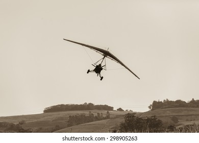 Flying Microlight Plane Landing Sepia Flying microlight aircrafts plane landing approach  on rural countryside grass airstrip in vintage sepia tone