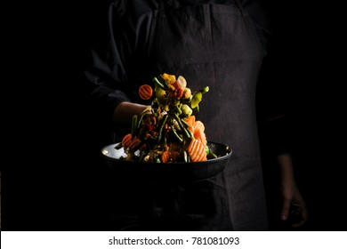Flying mixed vegetables on a pan. Diet healthy food. Black background for copy text.