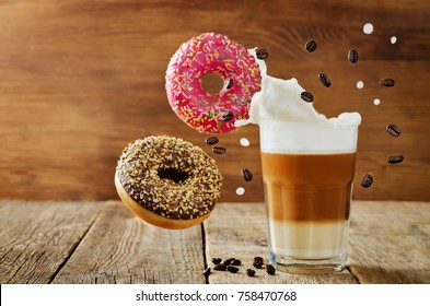 Flying multicolored donuts with a glass of coffee on a wood background. toning. selective focus