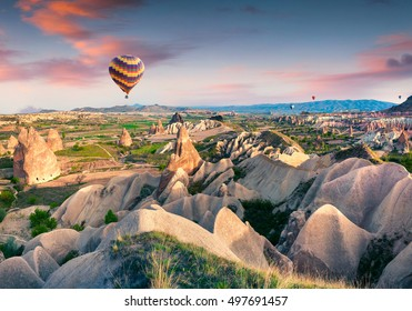 Flying on the balloons early morning in Cappadocia. Colorful sunrise in Red Rose valley, Goreme village location, Turkey, Asia. Artistic style post processed photo.