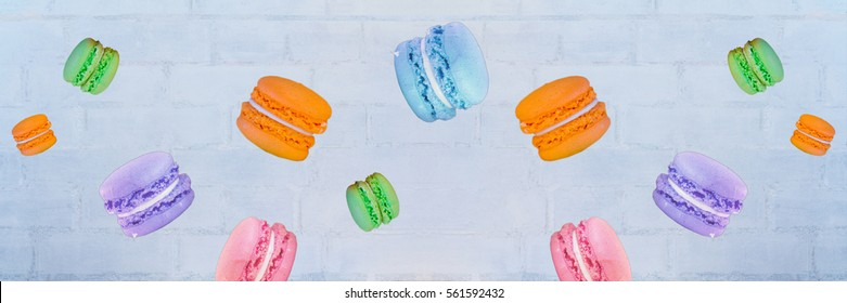 Flying orange, blue, pink, rose, violet and green macaroons - cookies - against blurred white brick wall. Top view. Selective focus. Copy space. Wide panoramic image. Joy and valentines day concept.