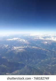 Flying over the Alps. An aerial view from the airplane over the mountains. Cloudscape and blue sky and atmosphere