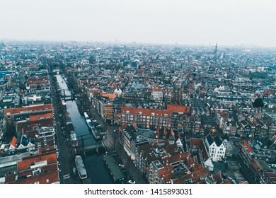 Flying over european city. From above view of old architectural buildings in city infrastructure with light haze above in gloomy day. Amsterdam.
