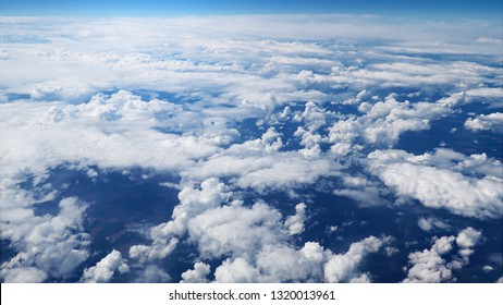 Flying over picturesque white clouds on the deep blue sky. Beautiful moving clouds view from airplane window. Traveling through clear blue cloudscape.