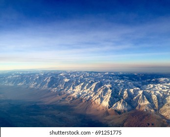 Flying over the Snowy Sierra Nevada Mountains in Winter at Sunrise