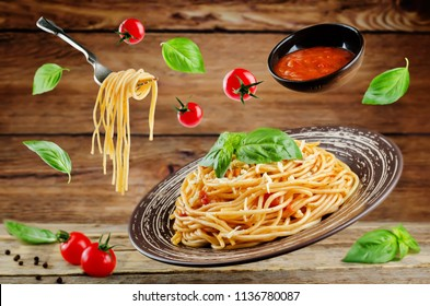Flying Pasta with Marinara sauce and fresh Basil on a wood background. toning. selective focus