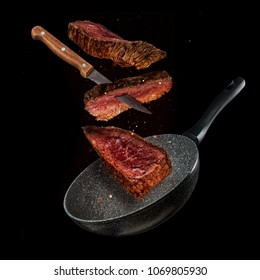 Flying pieces of beef steaks from pan, isolated on black background. Concept of flying food, very high resolution image