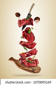 Flying pieces of raw beef steaks from cutting board, isolated on colored background. Concept of flying food, very high resolution image