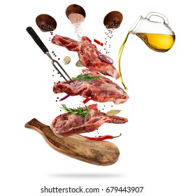 Flying pieces of raw pork steaks, with ingredients for cooking, served on woodenboard. Concept of food preparation in low gravity mode. Separated on white background. High resolution image