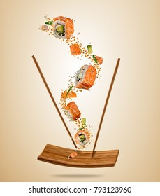 Flying pieces of salmon sushi with wooden chopsticks and plate, separated on beige background. Flying food and motion concept. Very high resolution image