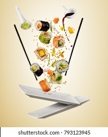 Flying pieces of sushi with wooden chopsticks, separated on beige background. Flying food and motion concept. Very high resolution image