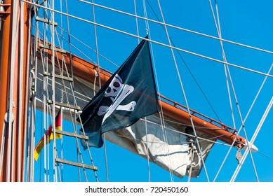flying pirate flag on three-master in port of sassnitz, ruegen island, germany