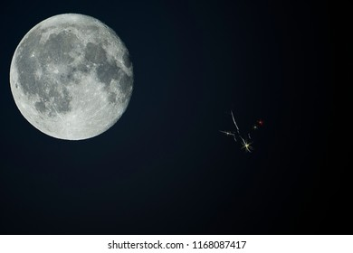 A flying plane at night on the huge moon background.