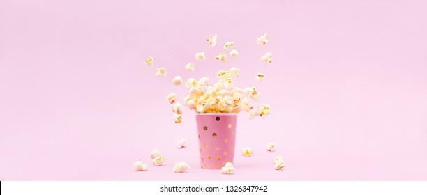 Flying Popcorn in a bright glass and on a pink background. Copy space