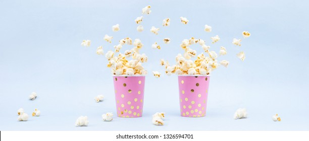 Flying Popcorn in a bright glass and on a blue background. Copy space