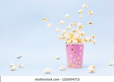 Flying Popcorn in a bright glass and on a blue background.