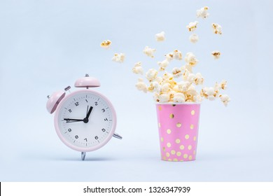 Flying Popcorn in a bright glass and a ringing alarm clock on a blue background. Time for a fun concept.