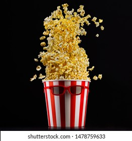 Flying popcorn from paper striped bucket and 3d glasses isolated on black background, concept of watching TV or cinema.