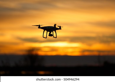 Flying quadrocopter drone is recording a sunset