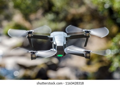flying quadrocopter on a background of green foliage, close-up