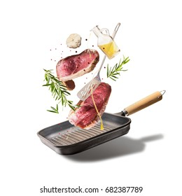 Flying raw beef steaks, with herbs, oil and spices with grill pan and kitchen utensils, isolated on white background, front view. Flying  food concept