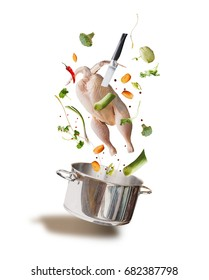 Flying raw chicken stock ,bouillon or soup ingredients with whole chicken, vegetables,seasoning, knife and cooking pot, front view, isolated on white background. Flying food concept