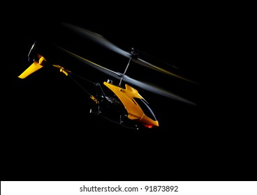 Flying RC helicopter on black