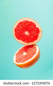 Flying red grapefruits on turquoise background. Grapefruits on blue background. Grapefruit in motion. Tropical fruit concept.